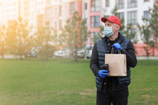 Uomo di consegna in berretto rosso, maschera medica per il viso, guanti tenere da asporto sacchetto di carta e bere in tazza usa e getta all'aperto in città
