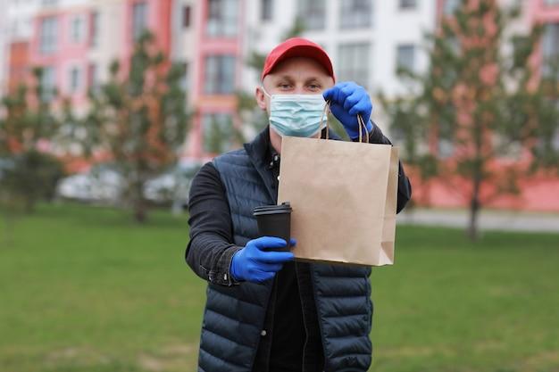 Uomo di consegna in berretto rosso, maschera medica per il viso, guanti tenere da asporto il sacchetto di carta e bere in tazza usa e getta