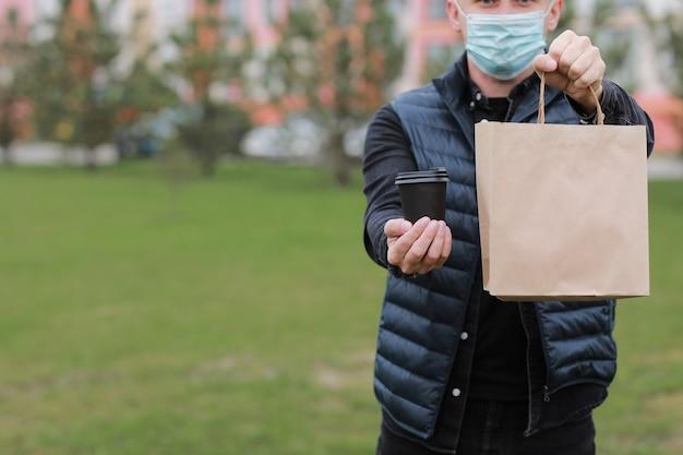 Fattorino in berretto rosso, maschera medica per il viso, tenere da asporto il sacchetto di carta e bere in tazza usa e getta