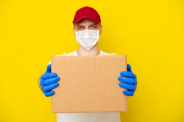 Il fattorino in guanti bianchi della maschera medica del fronte dell'uniforme della maglietta dello spiritello malevolo tiene la scatola di cartone vuota sulla parete gialla. servizio coronavirus. acquisti online. modello