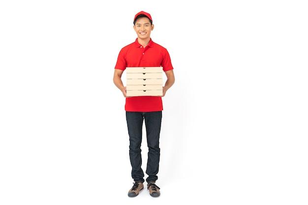 Uomo di consegna in uniforme di polo rossa in piedi con dare ordine di cibo e tenendo scatole per pizza