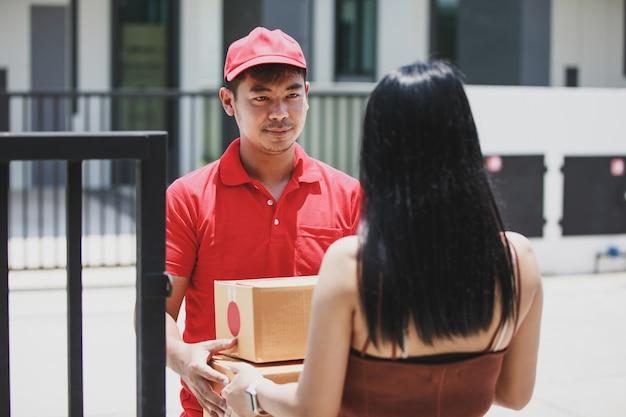 Fattorino in una maglietta rossa che tiene scatola di cartone