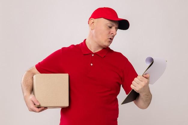 Fattorino in uniforme rossa e cappuccio con scatola di cartone e appunti guardandolo confuso in piedi su sfondo bianco