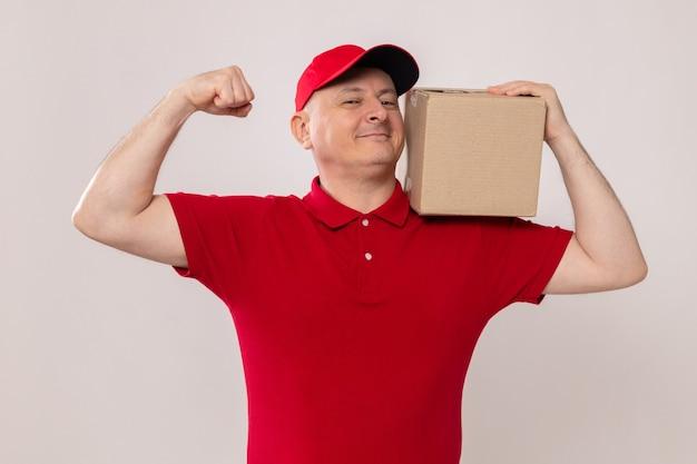 Fattorino in uniforme rossa e cappuccio che tiene una scatola di cartone sulla spalla guardando la telecamera sorridente fiducioso alzando il pugno come un vincitore in piedi su sfondo bianco