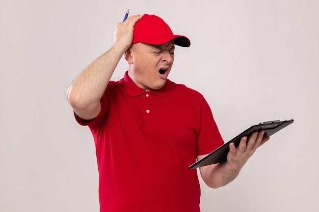 Fattorino in uniforme rossa e cappuccio che tiene appunti e penna guardando appunti stupito e confuso in piedi su sfondo bianco
