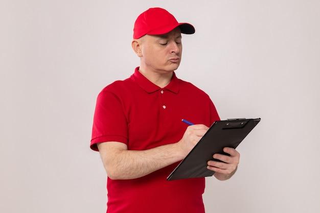 Fattorino in uniforme rossa e berretto che tiene appunti e penna che prende appunti con una faccia seria