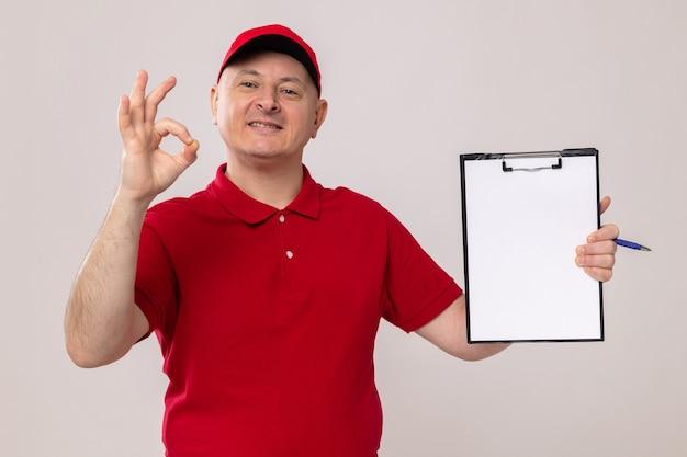 Fattorino in uniforme rossa e berretto che tiene appunti con pagine bianche che guardano la telecamera sorridendo allegramente mostrando segno ok in piedi su sfondo bianco