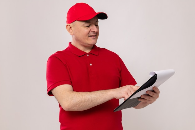 Fattorino in uniforme rossa e cappello che tiene appunti con pagine bianche che lo guardano con un sorriso sul viso