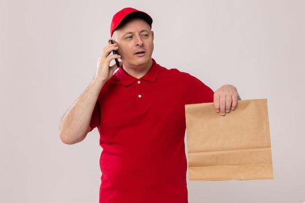 Fattorino in uniforme rossa e cappuccio che tiene in mano un pacchetto di carta che sembra sicuro mentre parla al telefono cellulare in piedi su sfondo bianco