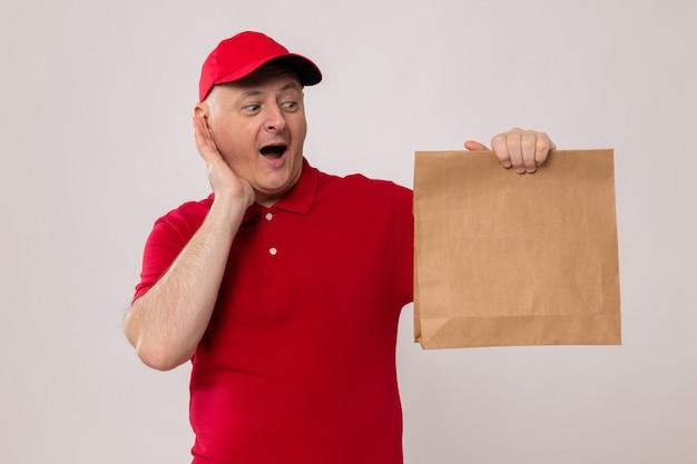 Fattorino in uniforme rossa e cappuccio che tiene in mano un pacchetto di carta guardandolo sorpreso e felice in piedi su sfondo bianco