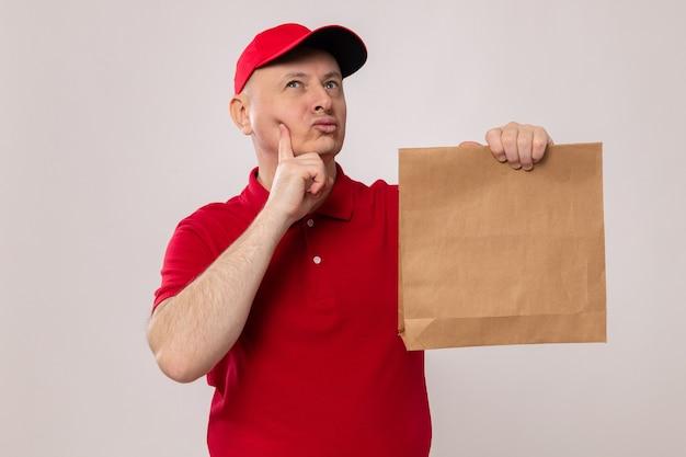 Fattorino in uniforme rossa e cappuccio che tiene il pacchetto di carta che osserva in su con espressione pensierosa pensando in piedi su sfondo bianco
