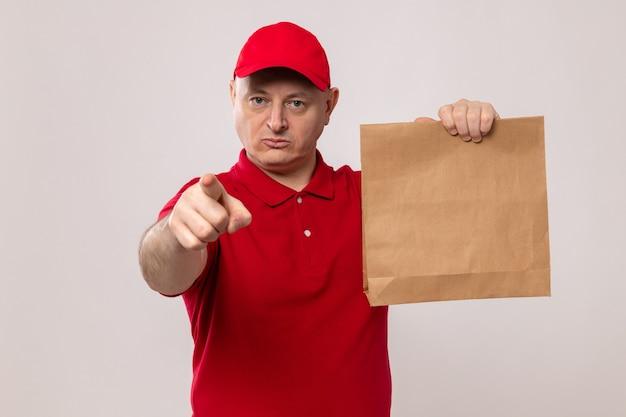 Uomo di consegna in uniforme rossa e cappuccio che tiene il pacchetto di carta che indica con il dito indice alla macchina fotografica con la faccia seria che sta sopra fondo bianco