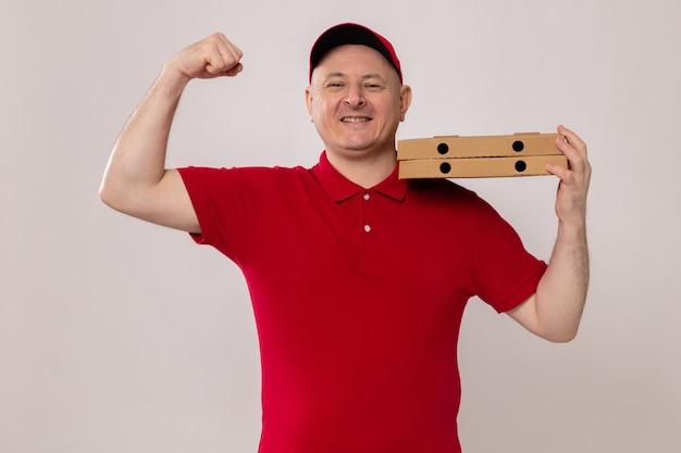 Fattorino in uniforme rossa e berretto che tiene scatole per pizza sulla spalla alzando il pugno come un vincitore felice e fiducioso che sorride allegramente in piedi su sfondo bianco