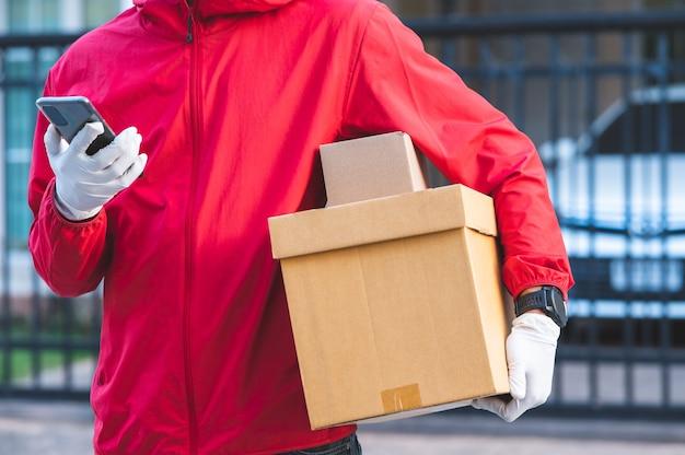 Fattorino in uniforme rossa guardate il telefono per trovare l'indirizzo del cliente tramite l'applicazione.