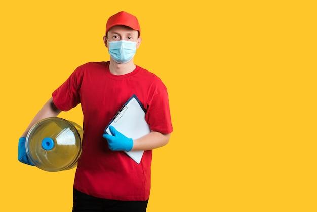 Fattorino in maschera uniforme rossa e guanti su colore giallo con bottiglia d'acqua e appunti