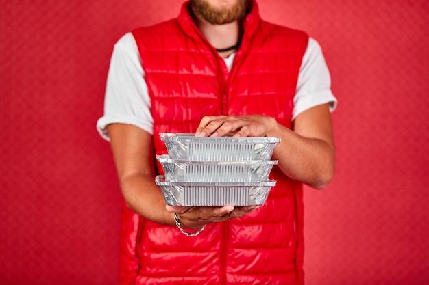 Il fattorino in tenuta uniforme della maglia rossa va il servizio di consegna del cibo della scatola isolato. ristoranti da asporto consegna di cibo alla porta di casa