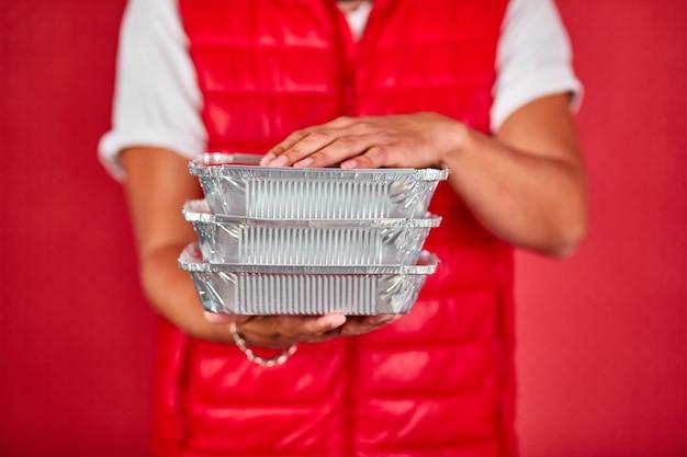 Il fattorino in uniforme della maglia rossa tiene la scatola del cibo, servizio di consegna, isolato
