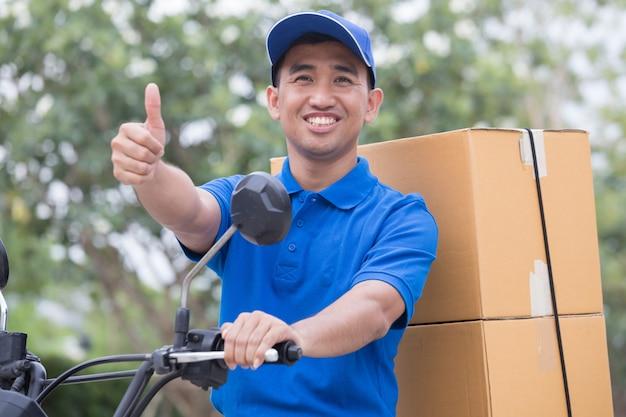 Il fattorino invia il pacco dell'ordine con motori e pollice in su