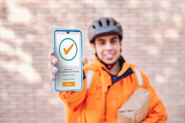 Il fattorino mostra lo schermo di un telefono con la conferma della spedizione