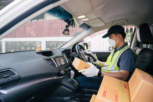 Un fattorino che usa un lettore di carte di credito. nel furgone con i pacchi all'esterno del magazzino. consegna