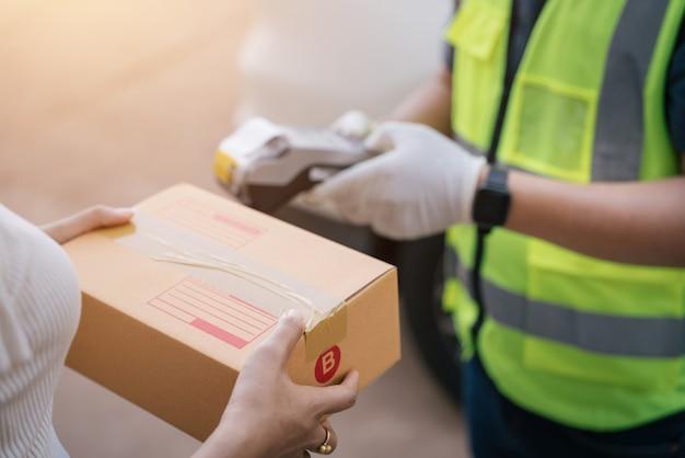 Un fattorino che utilizza un lettore di carte di credito durante la consegna di prodotti ai clienti a casa, concetto di contrassegno con carta di credito.