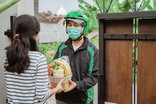 Uomo di consegna indossare maschera durante la consegna di cibo
