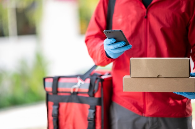 Uomo di consegna che indossa guanti blu in panno rosso alla ricerca dell'indirizzo del cliente dal telefono cellulare