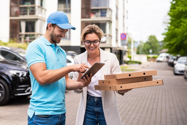 Il fattorino che indossa l'uniforme blu consegna la pizza a una donna clie