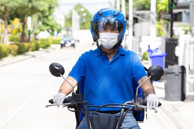 Uomo di consegna che indossa uniforme blu in sella moto e scatola di consegna moto