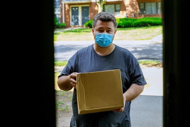 Fattorino con maschera facciale che consegna una scatola di cartone all'ingresso della consegna a domicilio durante la quarantena della pandemia di coronavirus.