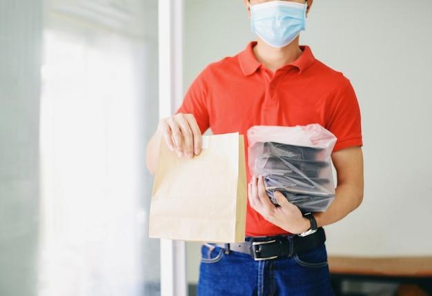 Uomo di consegna che indossa la maschera per il viso e mano che tiene l'imballaggio alimentare servizio di consegna di cibo a casa