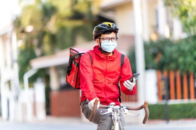 Uomo di consegna che indossa una maschera protettiva per il viso per evitare il virus corona guardare il telefono per trovare l'indirizzo del cliente tramite l'applicazione.