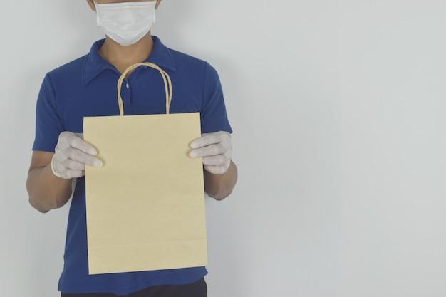 Fattorino che indossa maschera e guanti medici che tengono il sacchetto di carta su sfondo bianco