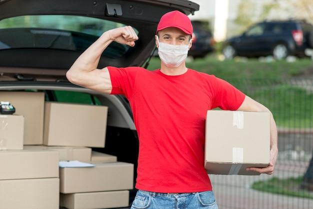 Uomo di consegna che indossa una maschera medica