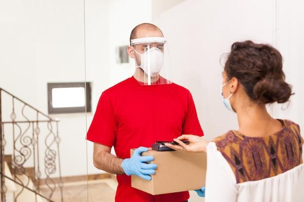 Fattorino che indossa una maschera di protezione mentre la donna paga il pacco.