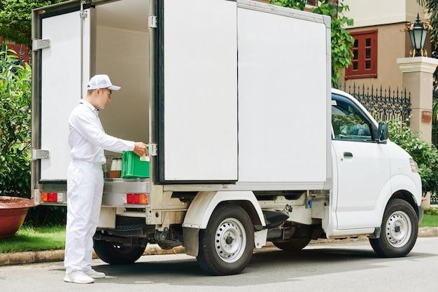 Fattorino in uniforme bianca prendendo cassa di plastica con bottiglie di latte in vetro dal bagagliaio del furgone