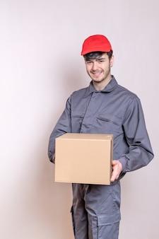 Fattorino con scatola di cartone in mano che consegna l'ordine, vestito in uniforme e sorridente, con berretto rosso