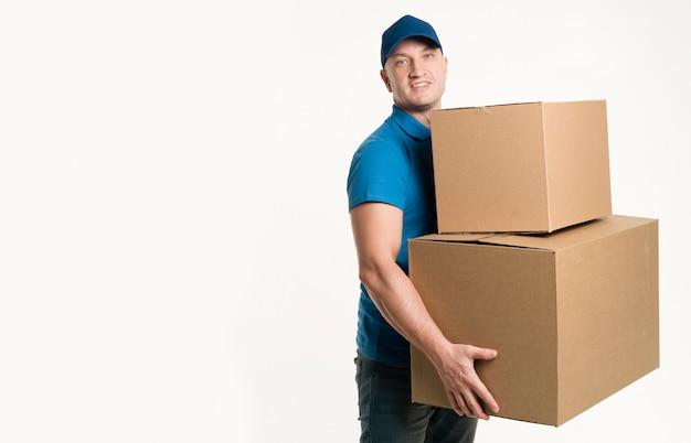 Uomo di consegna con scatole di cartone e copia spazio