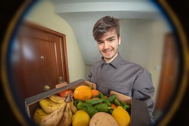 Fattorino con scatola di frutta tra le mani che consegna l'ordine, vestito in uniforme e sorridente, cliente che guarda attraverso lo spioncino