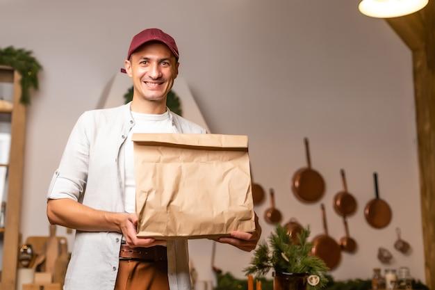 Un fattorino con un pacco di bancarelle di cibo in un interno di natale