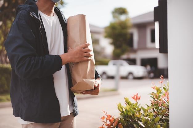 Fattorino con maschera protettiva consegnare generi alimentari e cibo in un sacchetto di carta riutilizzabile da vicino con copyspace