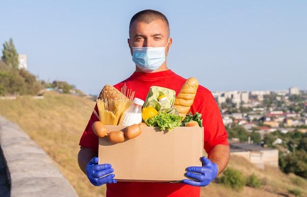 Uomo di consegna con maschera protettiva e guanti che tengono una scatola con generi alimentari freschi