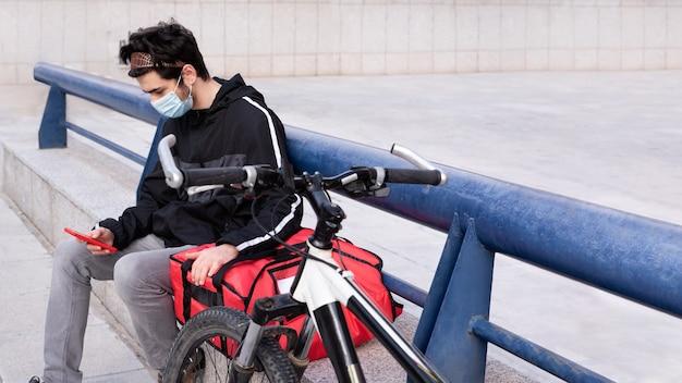 Uomo di consegna con borsa rossa e bici seduta, usa il suo telefono cellulare per effettuare l'ordine successivo in bicicletta