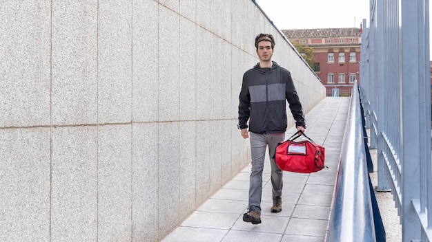 Fattorino con borsa rossa che cammina per fare una consegna a domicilio
