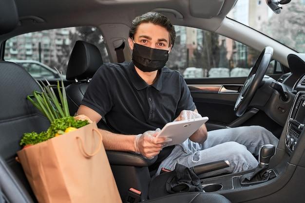 Fattorino con tablet in maschera protettiva e guanti consegnati verdure fresche dal negozio
