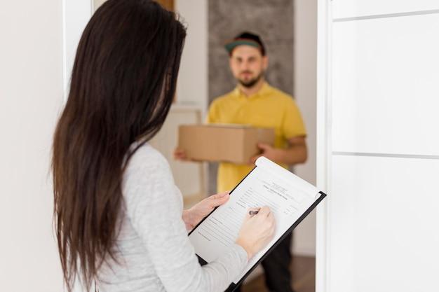 Uomo di consegna e donna davanti alla porta