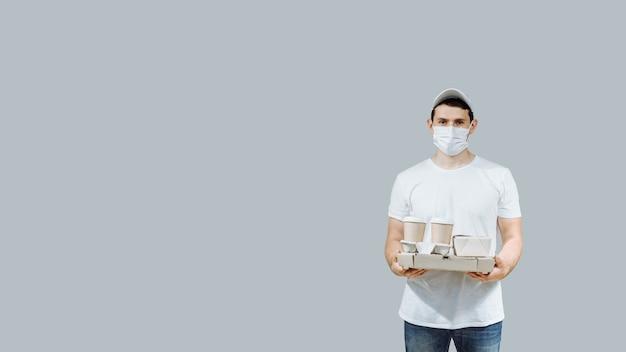 Il lavoratore del fattorino con i guanti della maschera dell'uniforme della maglietta bianca del berretto dà le scatole della pizza e il caffè di ordine alimentare