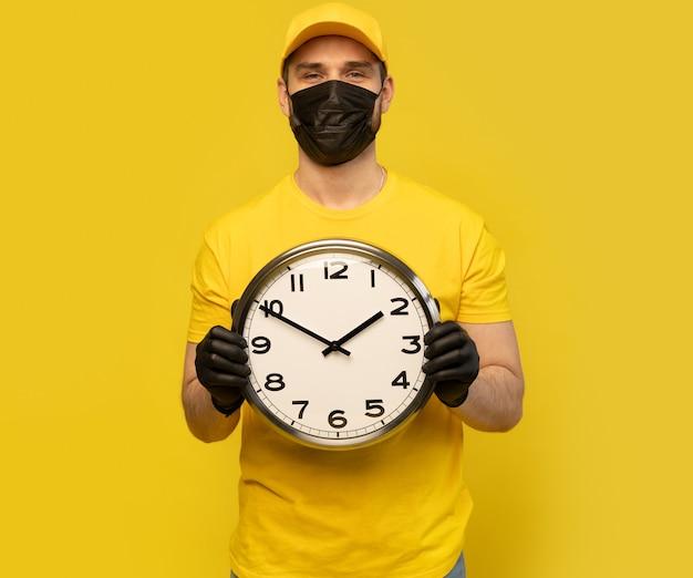Fattorino in abbigliamento da lavoro giallo tenere l'orologio isolato. impiegato maschio professionista in stampa maglietta cappuccio lavorando come corriere rivenditore
