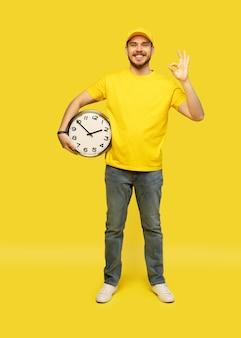 Uomo di consegna in abbigliamento da lavoro giallo tenere l'orologio isolato su sfondo giallo ritratto in studio.