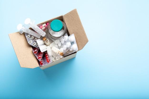 Consegna dei medicinali a domicilio dalla farmacia. scatola di cartone con medicinali, pillole, bottiglie, iniezioni isolate su vista dall'alto di sfondo blu